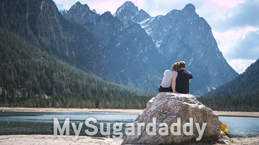 casal passando tempo de qualidade apreciando paisagem montanhosa