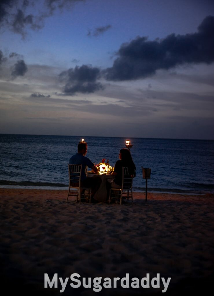 A couple spending quality time together at the beach. They are dining by candlelight.