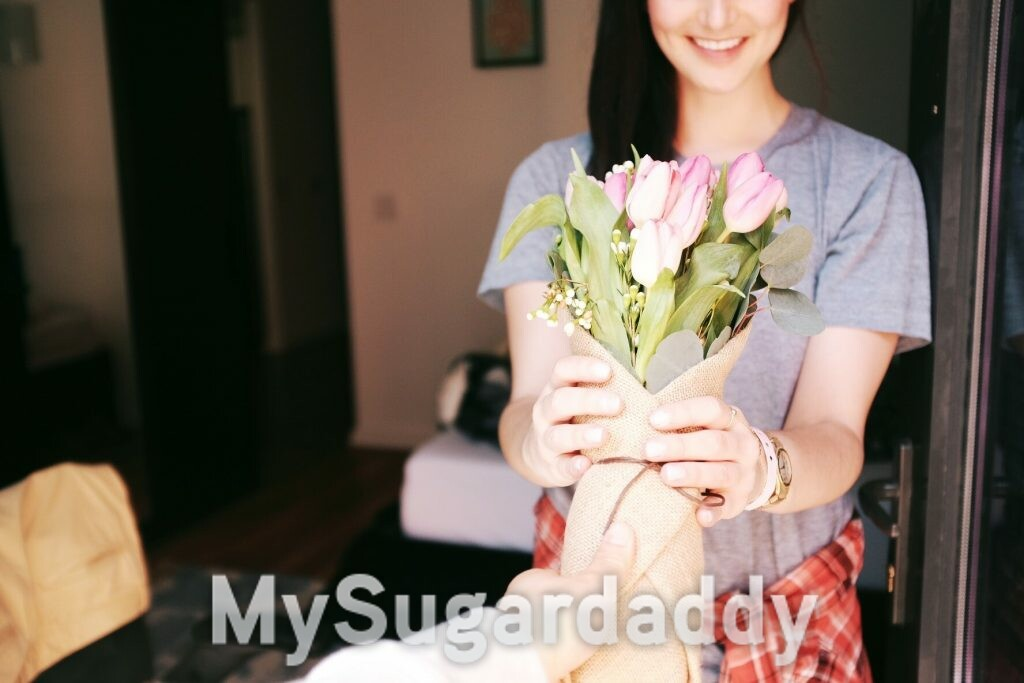 A woman receiving flowers as a gift