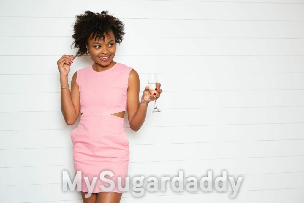 sugar baby de vestido rosa com taça de champanhe na mão