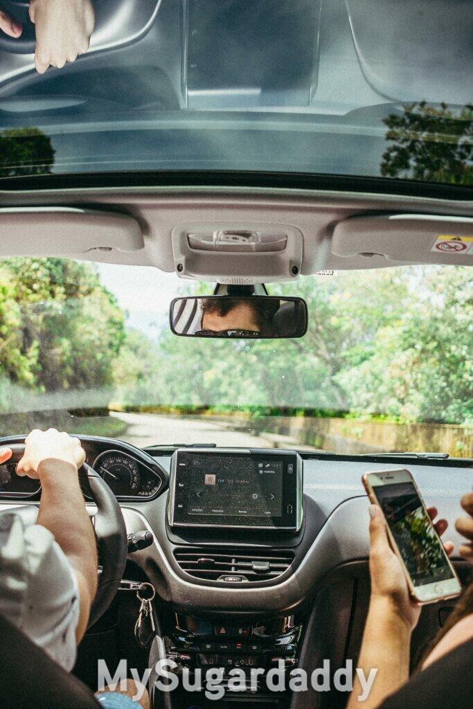 homem e mulher no carro com celular